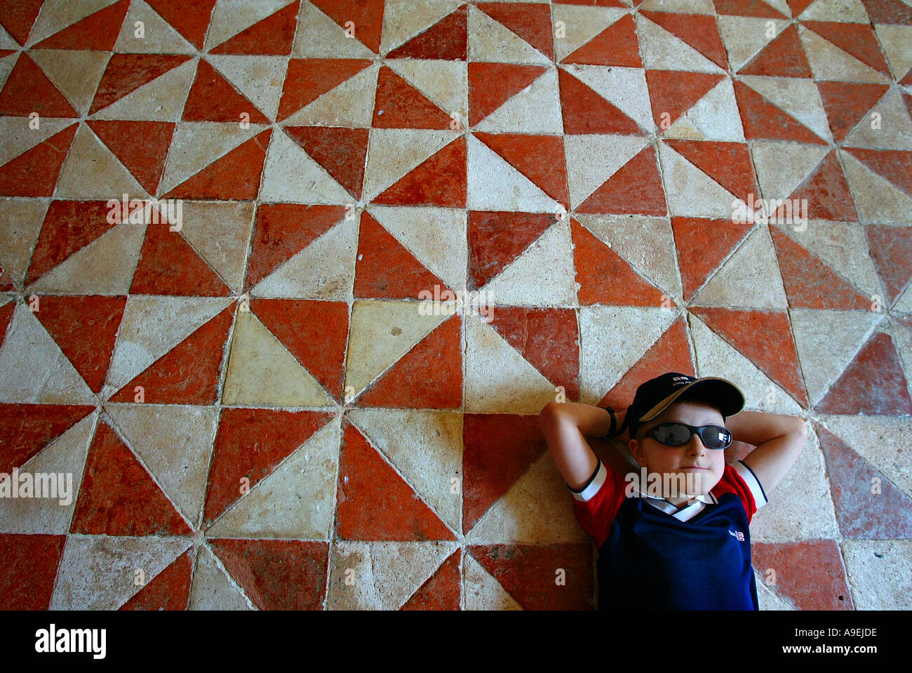A youngster rests on the elizabethan floor at Buckland Abbey near Tavistock UK, home of Sir Francis Drake. - Stock Image