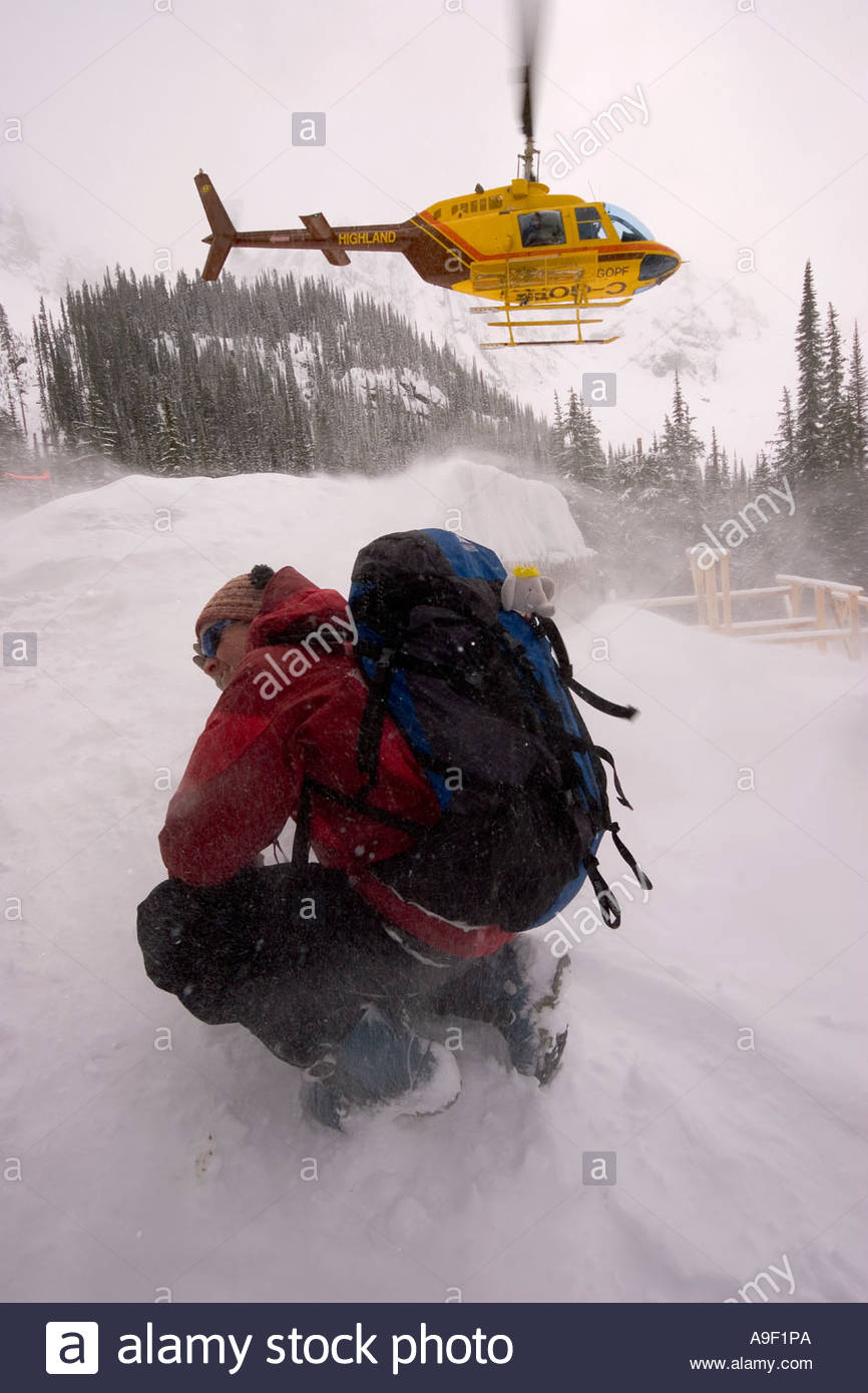Female skier hunkering down in the jetwash from the heli Ice Creek Lodge Valhalla Mountains British Columbia Canada - Stock Image