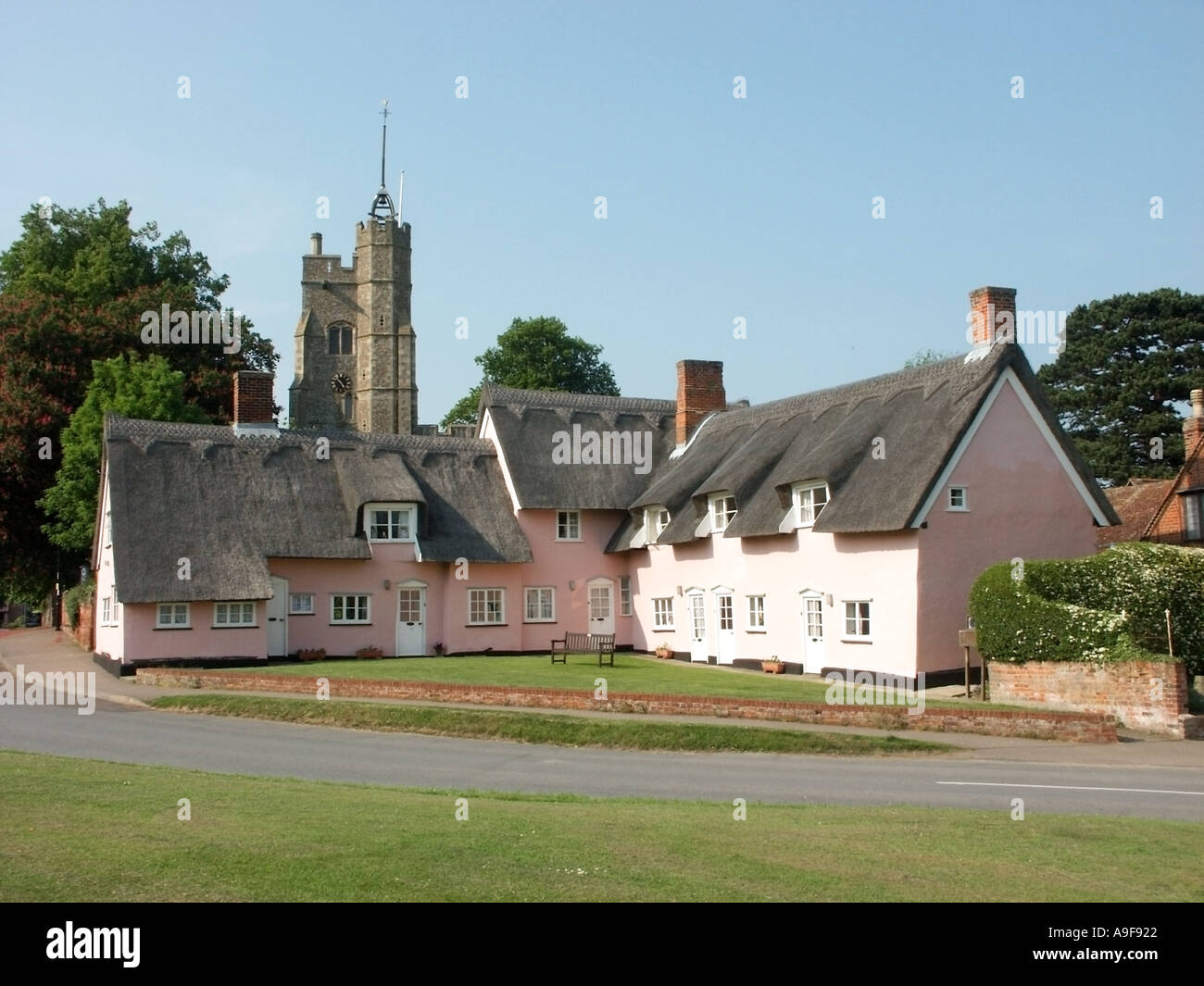 Cavendish near Sudbury thatched roofs on Alms Houses beside village green church tower beyond Suffolk East Anglia England UK - Stock Image