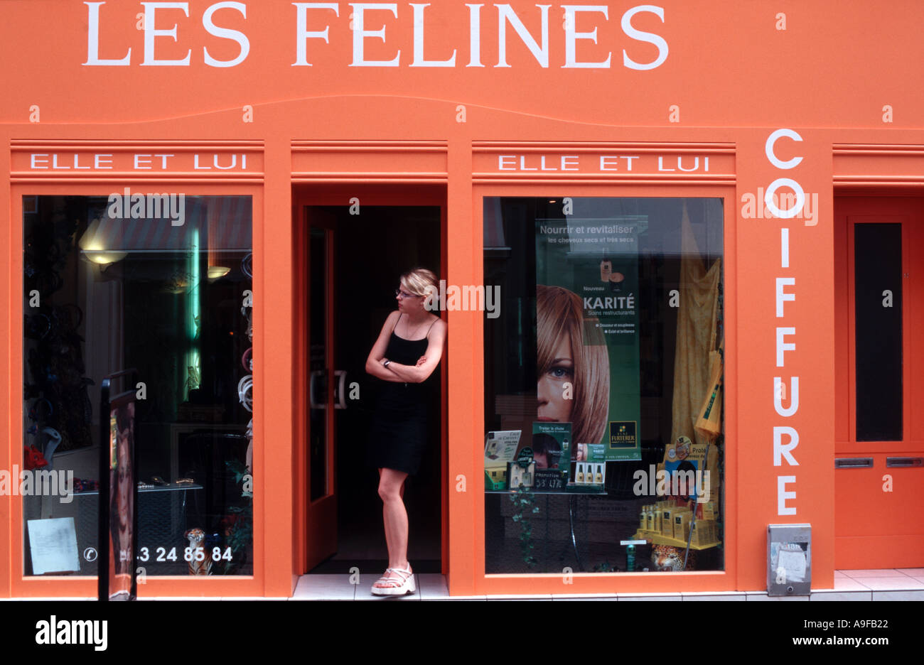 Hair Stylist Standing Outside A French Hair Salon As If Looking For