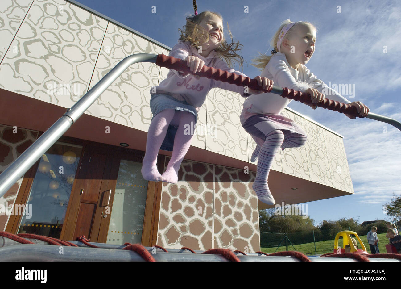 Two four 4 year old girls bounce with glee on a trampoline - Stock Image