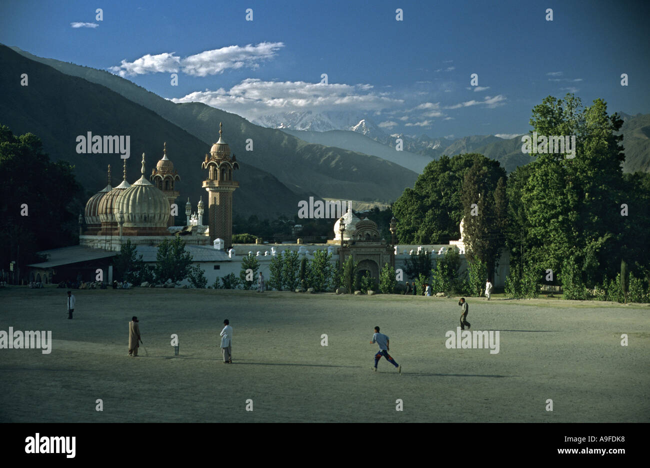 Men playing cricket in Chitral North West frontier region Pakistan View of Mosque and snow capped Afghanistan mountains in dista - Stock Image