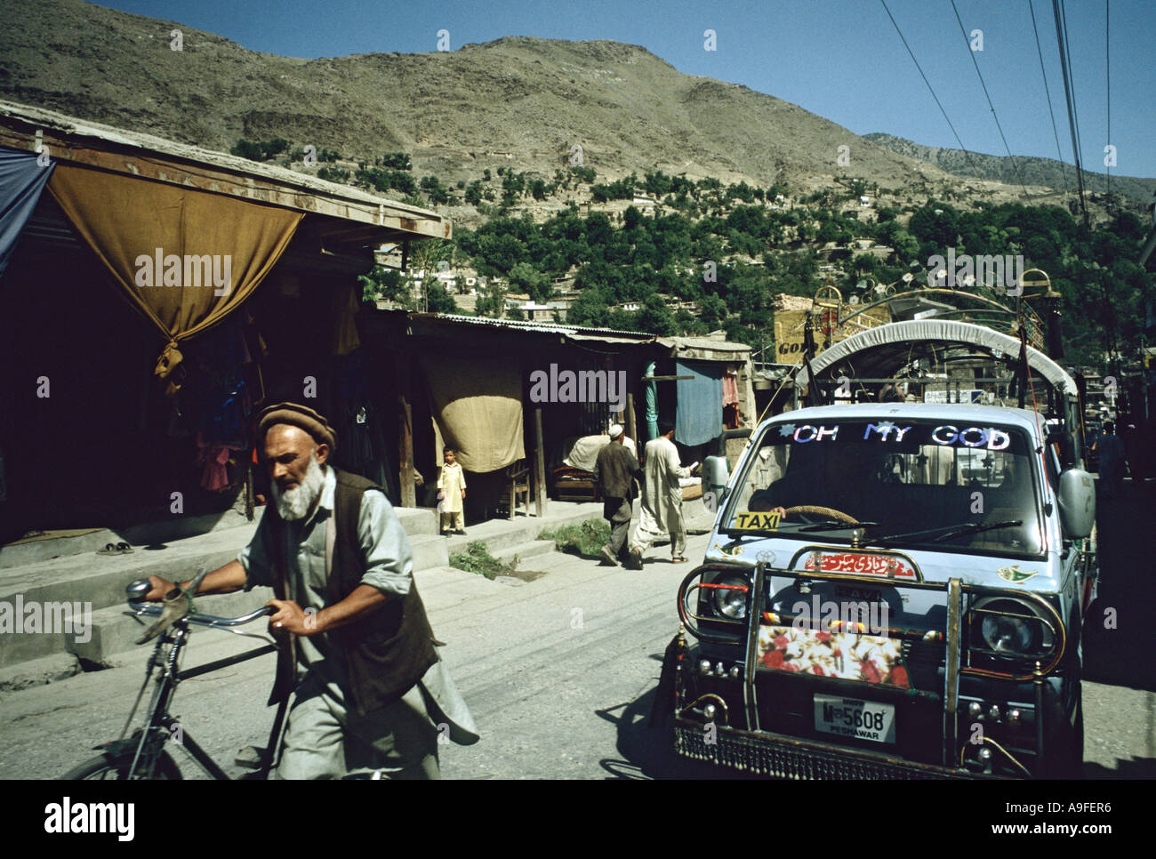Old man with beard pushes bicycle small transporter bus with words Oh My God on windscreen Chitral North West Frontier pakistan - Stock Image