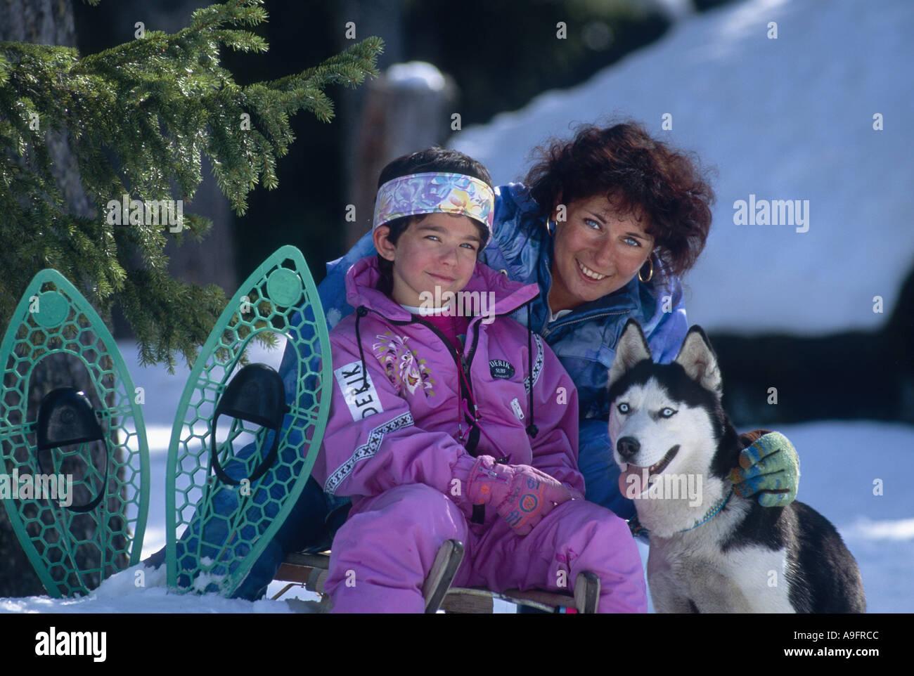 woman, siberian husky and girl on sled. Stock Photo