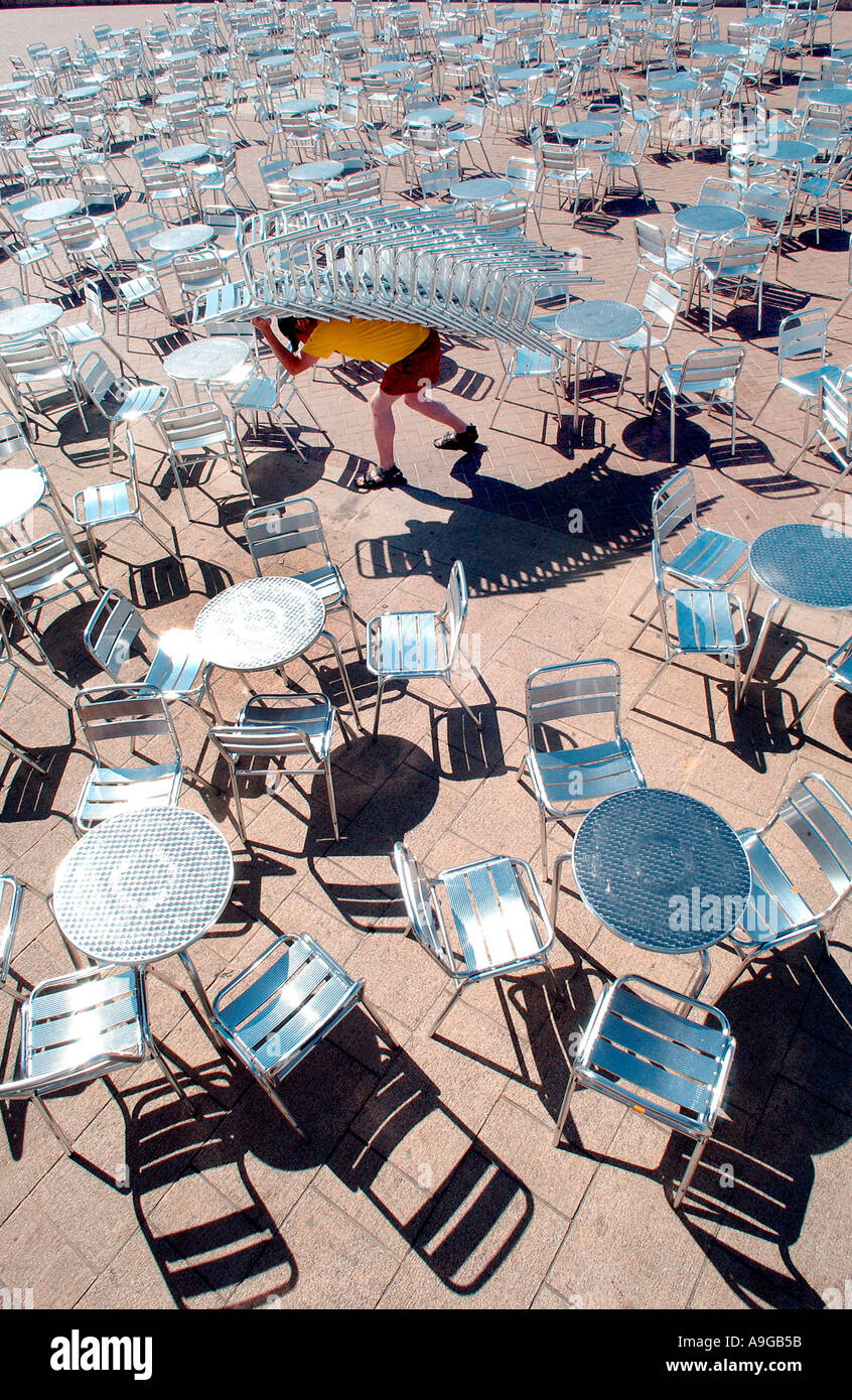 A young man hauls a stack of 16 metal chairs across the terrace in front of Gemini Lounge and Beach Bar on Brighton Stock Photo