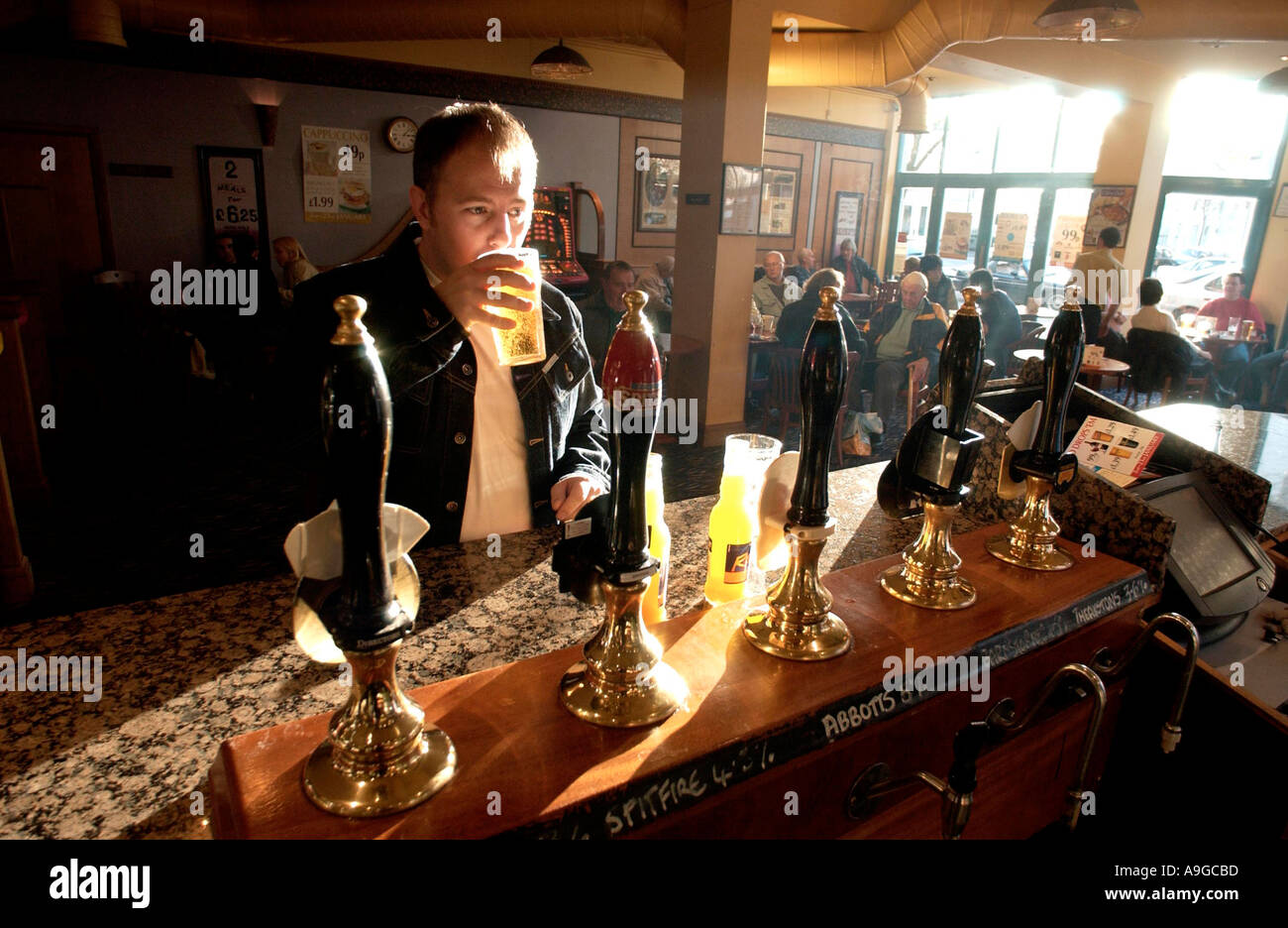 A man sinking a quiet pint in a traditional English pub on a sunny afternoon - Stock Image