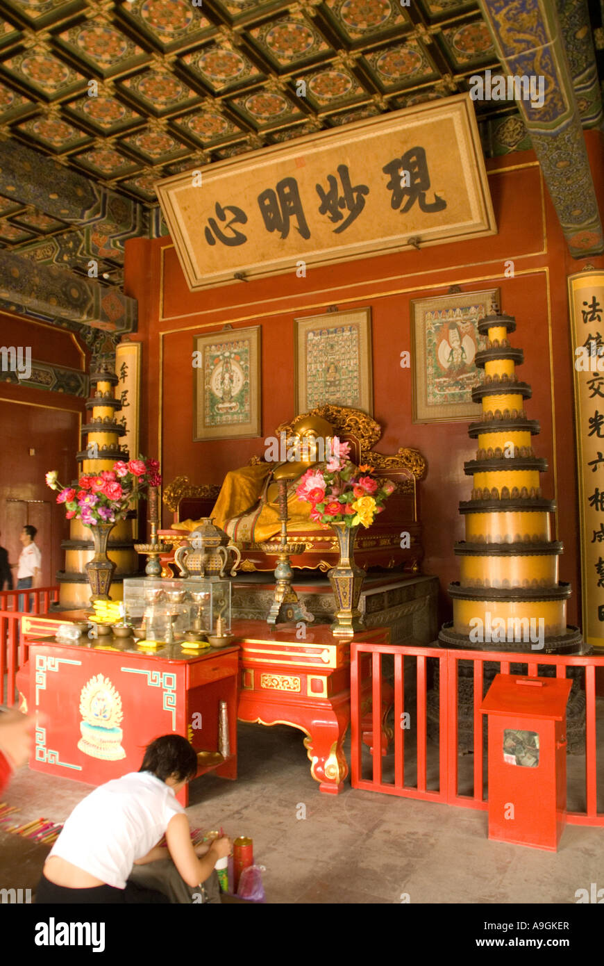 The Lama Temple (Yonghe Gong) interior of a hall with worshipper - Stock Image
