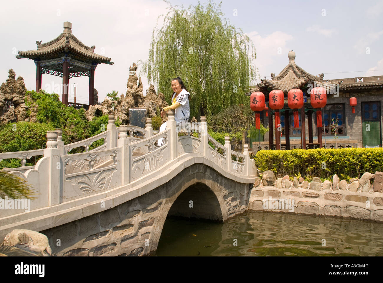 Classical Chinese garden with pond and stone bridge at Qiao Family ...