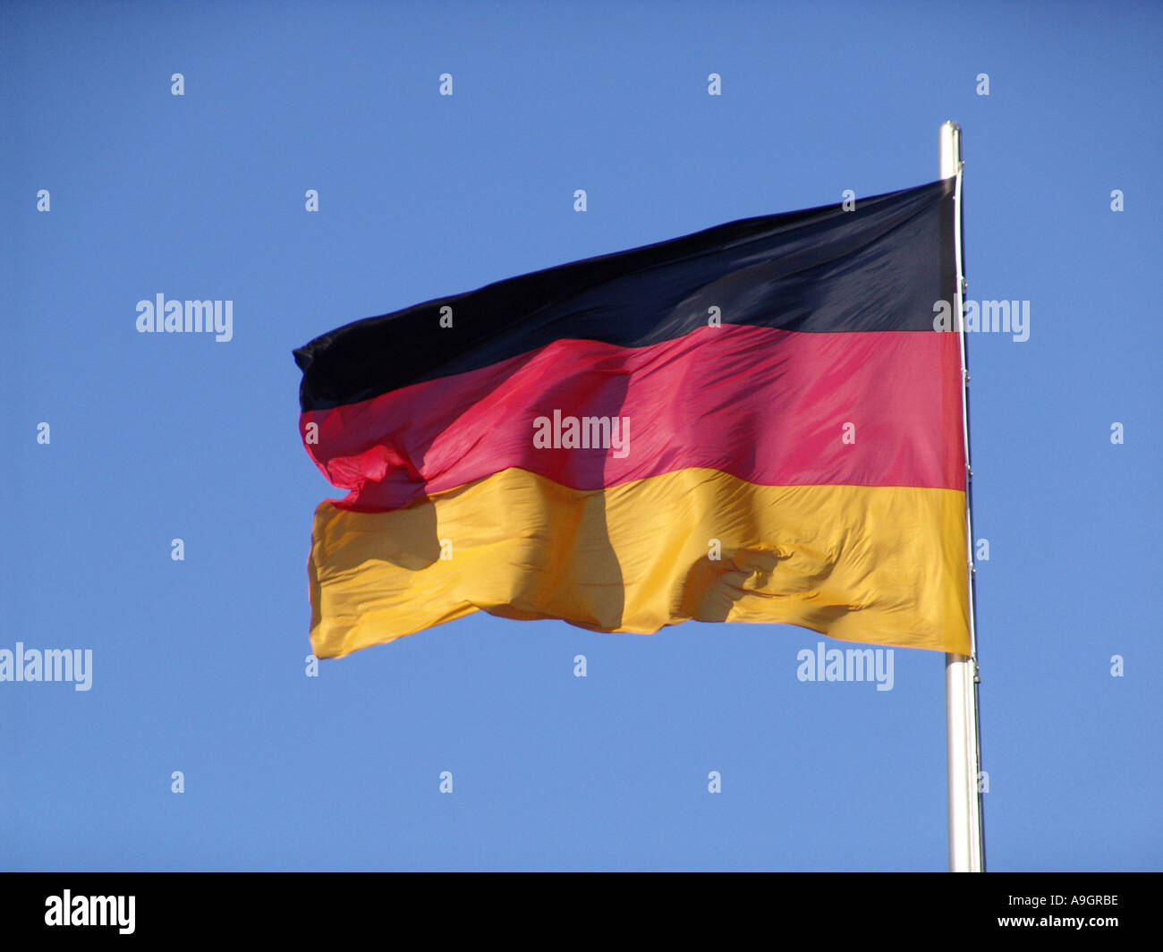 german flag, with blue sky behind, Germany, Berlin, Feb 04. - Stock Image