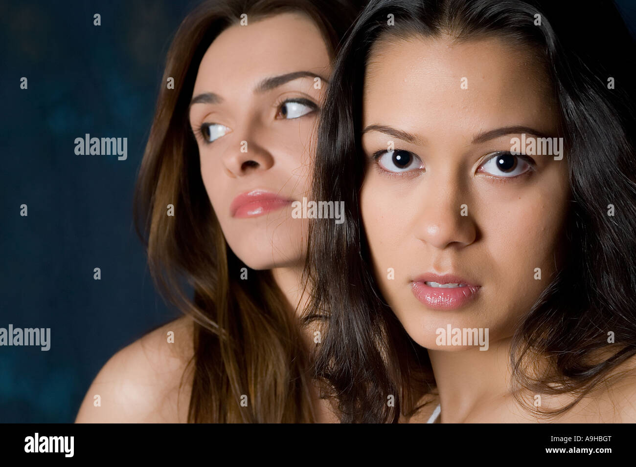 two brunette models with focus on one and serious expressions - Stock Image