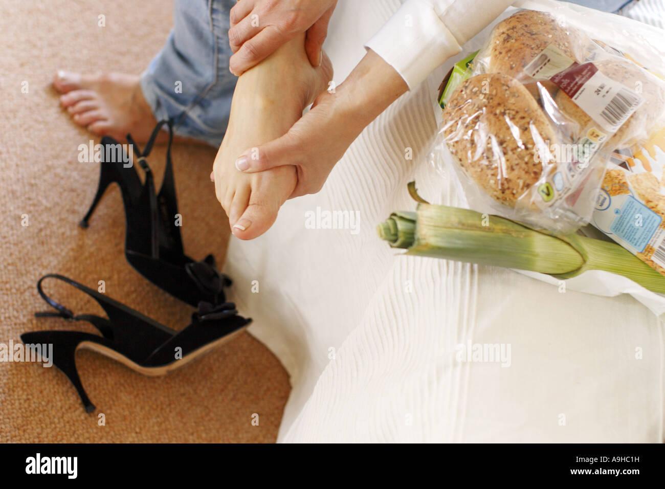 Woman massaging aching feet - Stock Image
