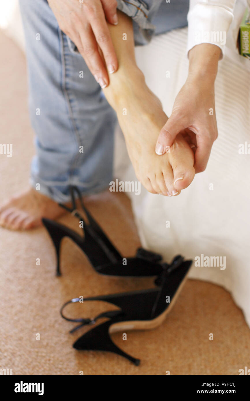 Woman massaging aching feet - Stock Image