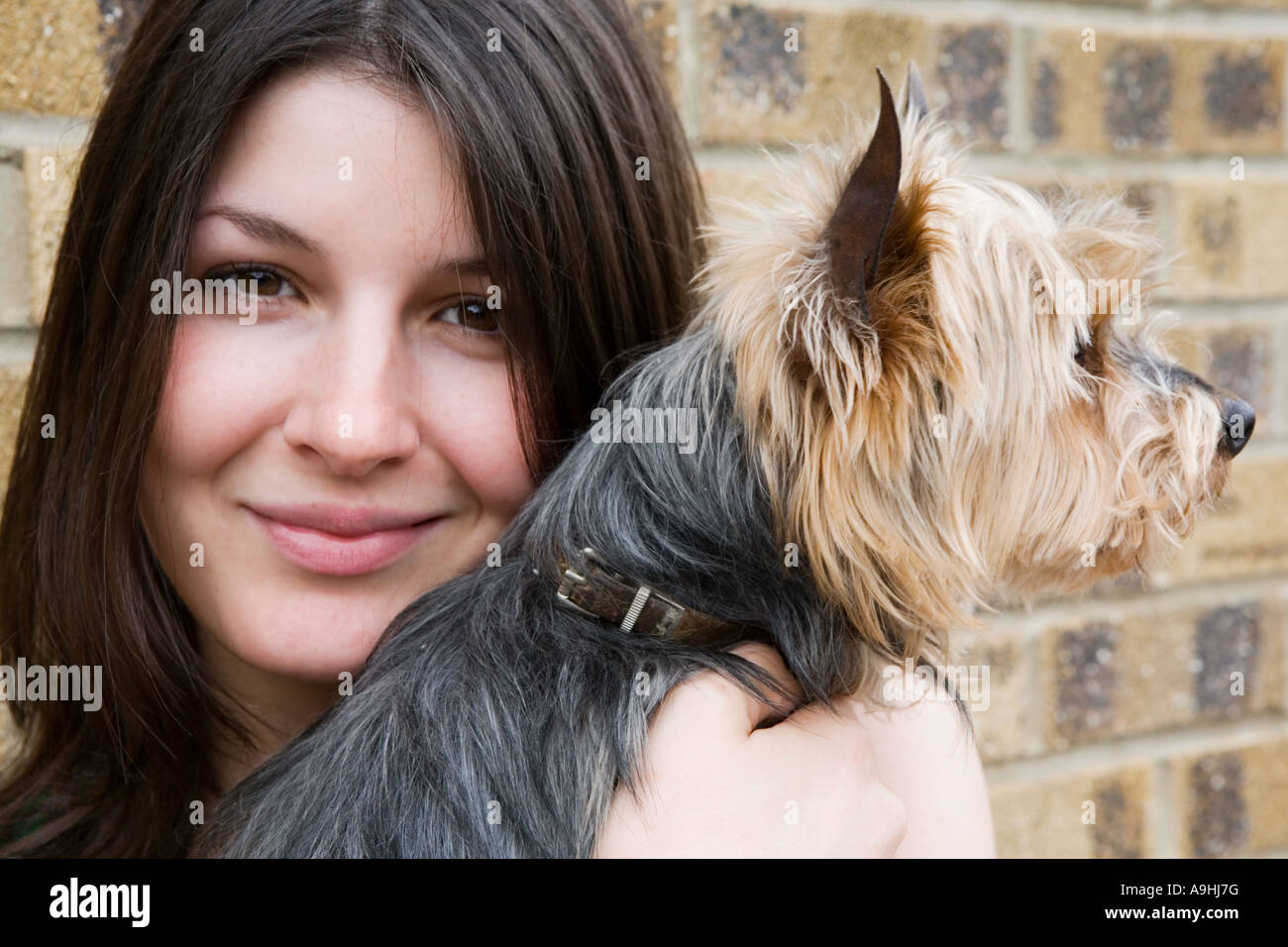Girl holding her small dog - Stock Image