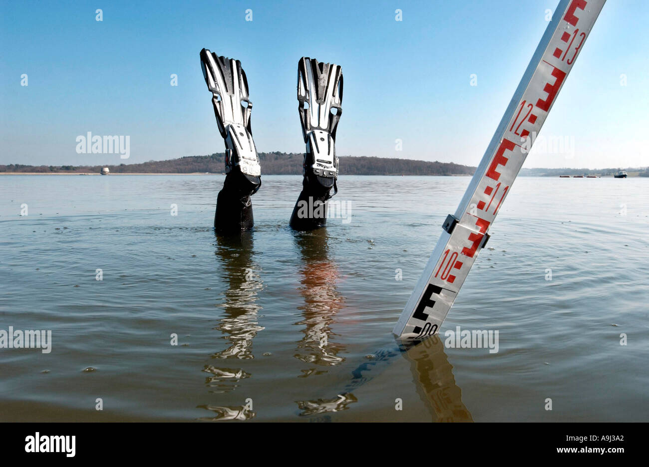 Diver Paul Jackman uses a depth rod to measure the capacity of a reservoir where water levels are low because of a dry summer. - Stock Image