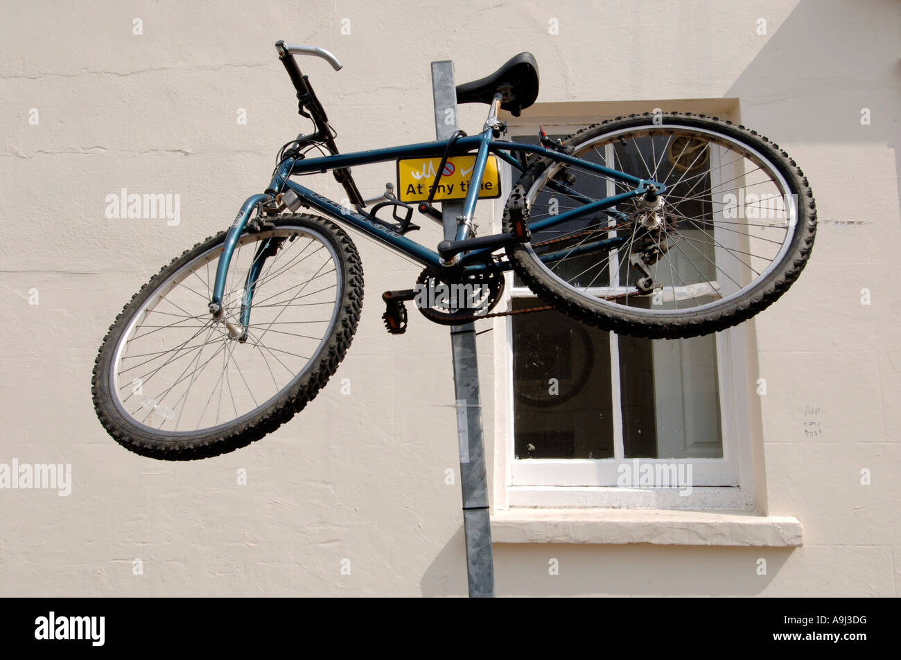 A Raleigh Mountain bike is secured on top of a parking restriction pole on a city road. - Stock Image