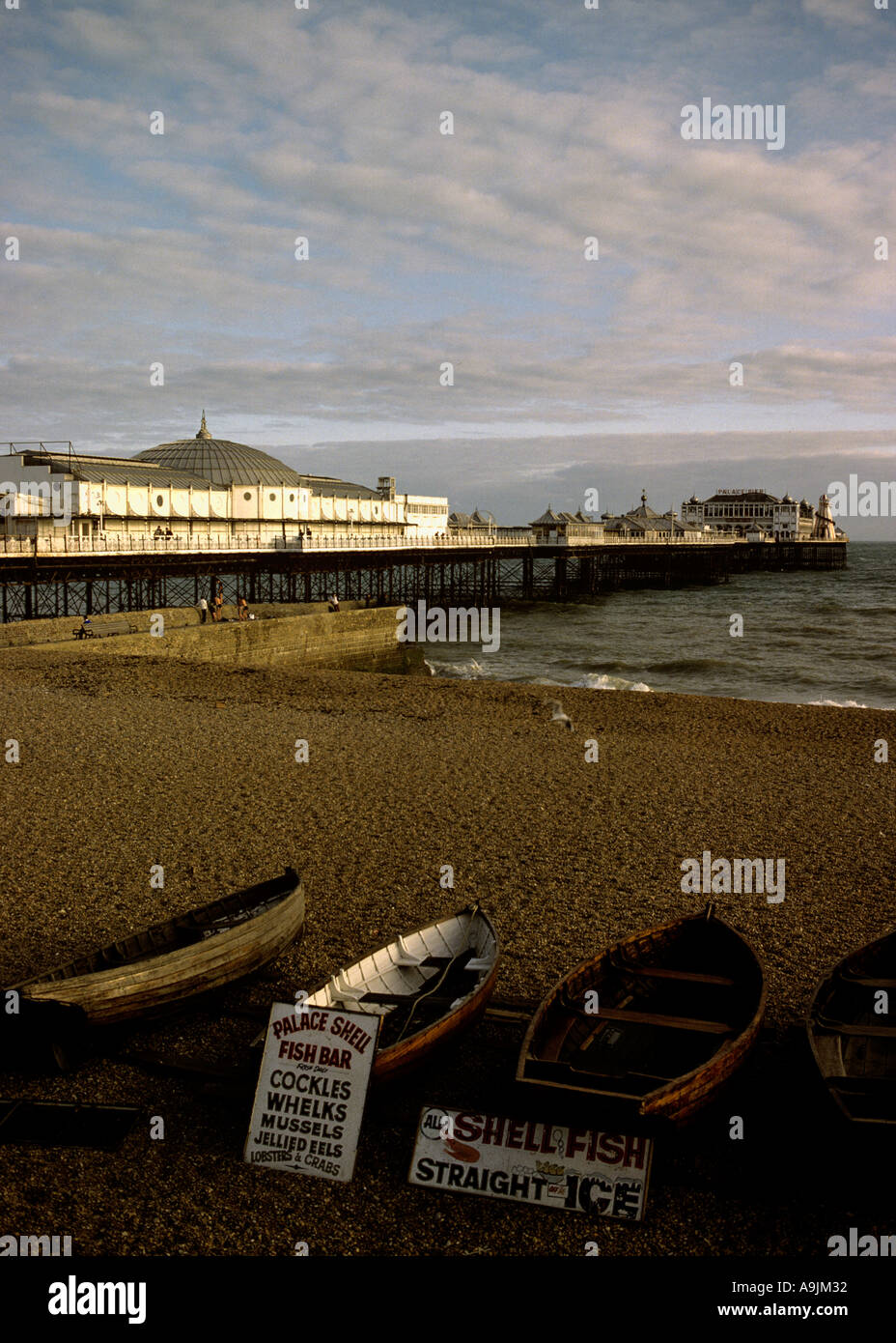 Victorian amusement pier on the seaside Brighton small wooden rownung boats pulled up on the shingle beach Shell Stock Photo