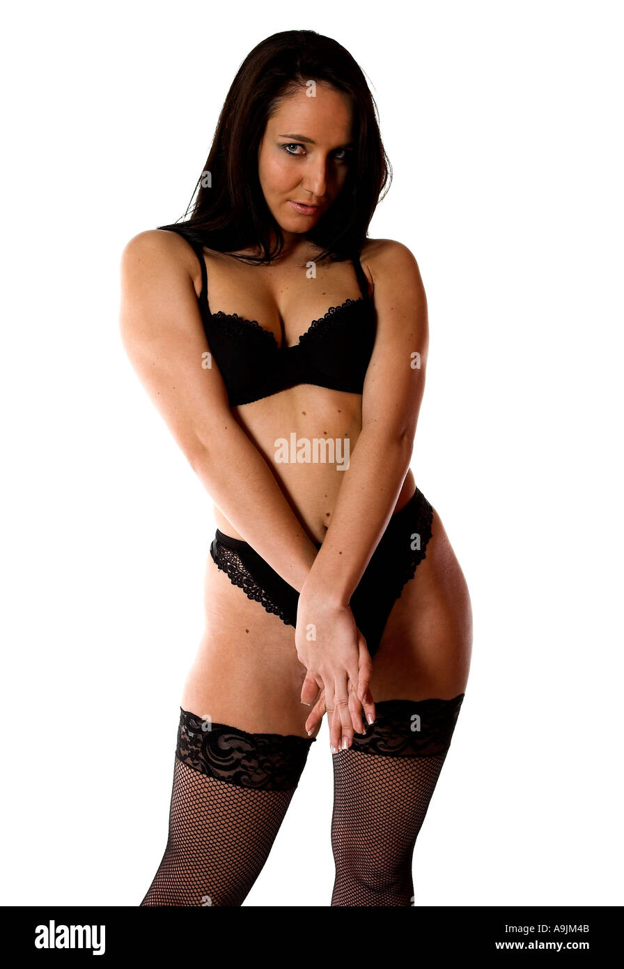 a50b77ab711 A female model with long black hair wearing classic black lingerie poses  against a white background