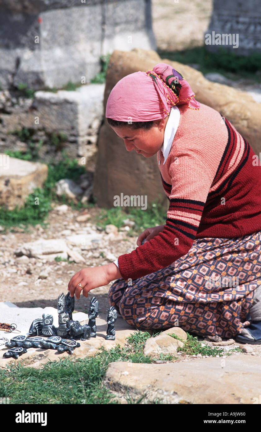 Turkish woman selling small stone carved souvenirs at the Roman ruins of Perge near Antalya Turkey Settled c 1500BC - Stock Image