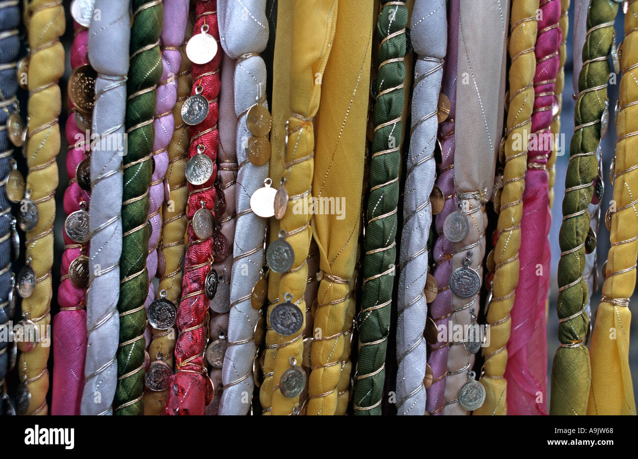 Detail of stacks of braided silk ribbons with applique coin decoration for sale at souvenir market in Turkey - Stock Image