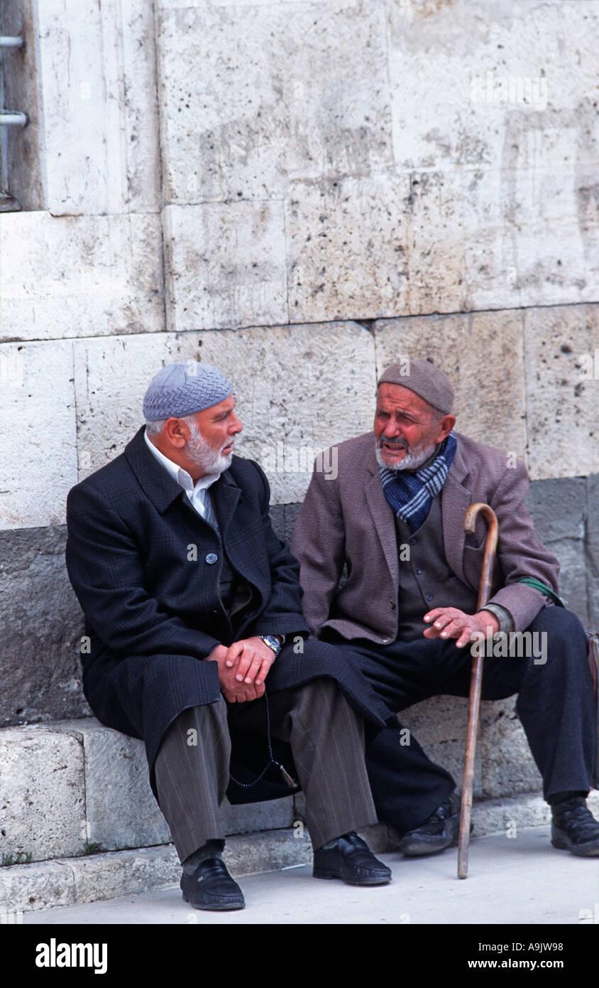Two Turkish men sitting chatting Konya Central Anatolia Turkey Seated outside the Dervish museum - Stock Image
