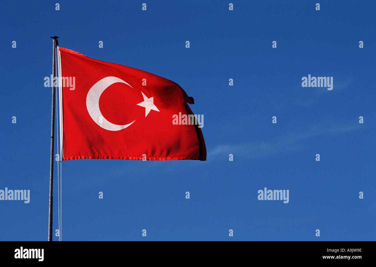The Turkish National flag flowing in the wind against a clear blue sky Turkey - Stock Image
