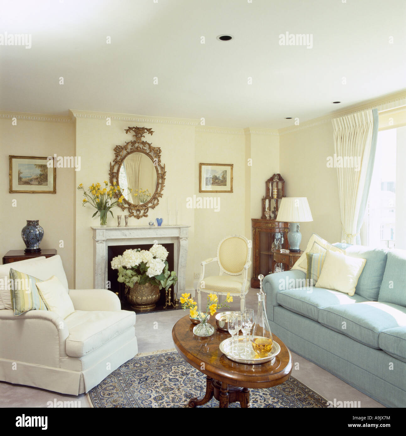 White armchair and pastel blue sofa in pale yellow sitting room with ...