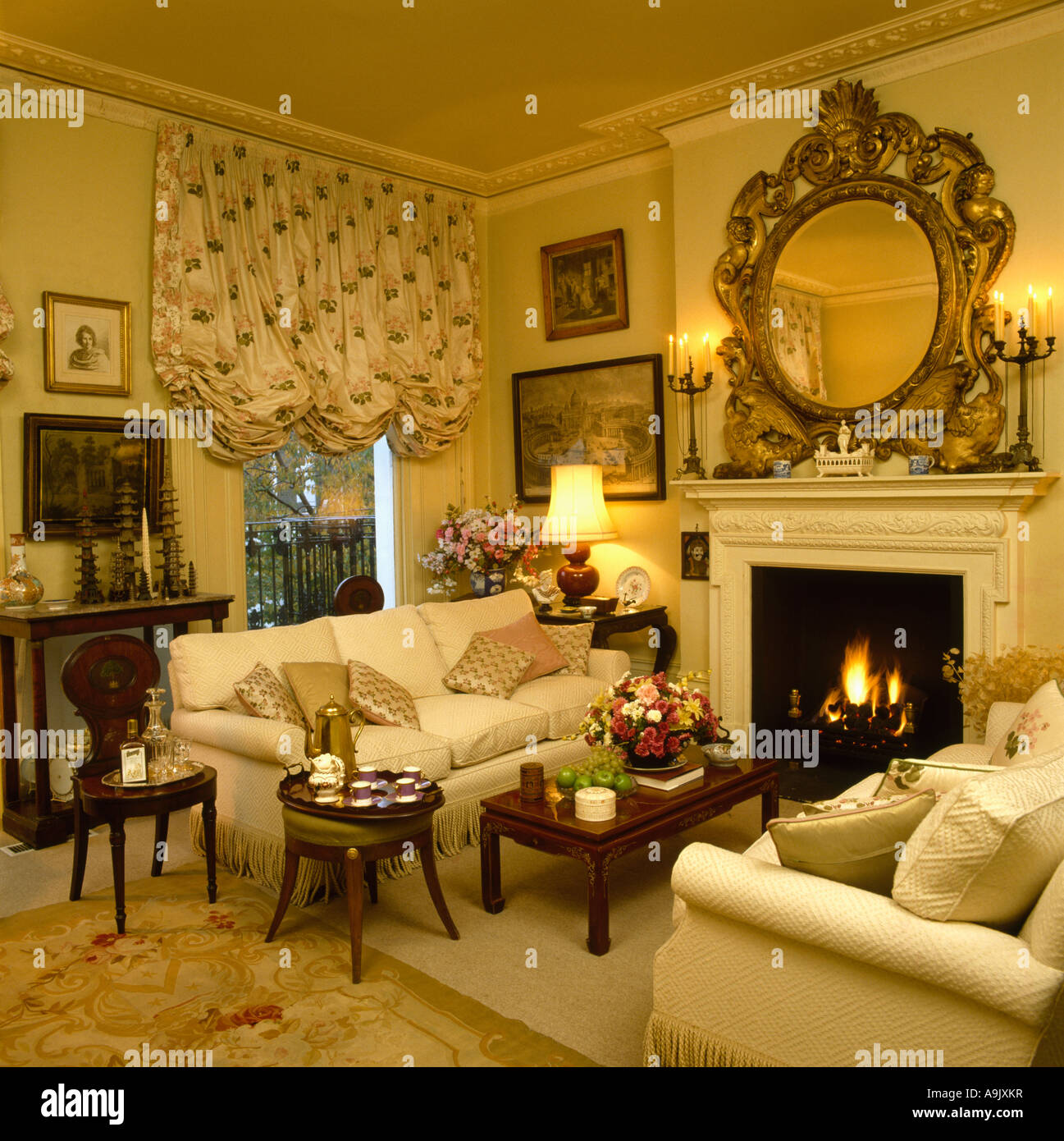 Large ornate gilt mirror above fireplace with fire lit in cream ...