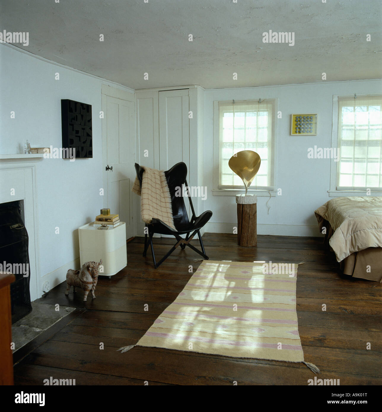 white bedroom with dark furniture. Cream Rug On Dark Wood Polished Floor In White Bedroom With Leather Butterfly Chair And Modern Bronze Sculpture Plinth Furniture M