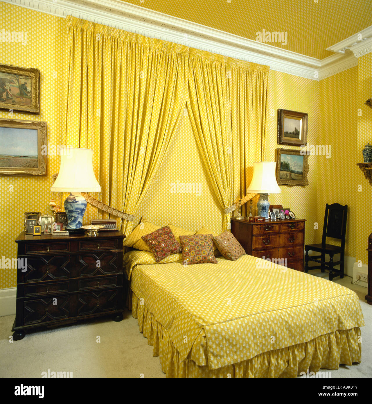 Yellow curtains on wall behind bed with yellow bedlinen in ...