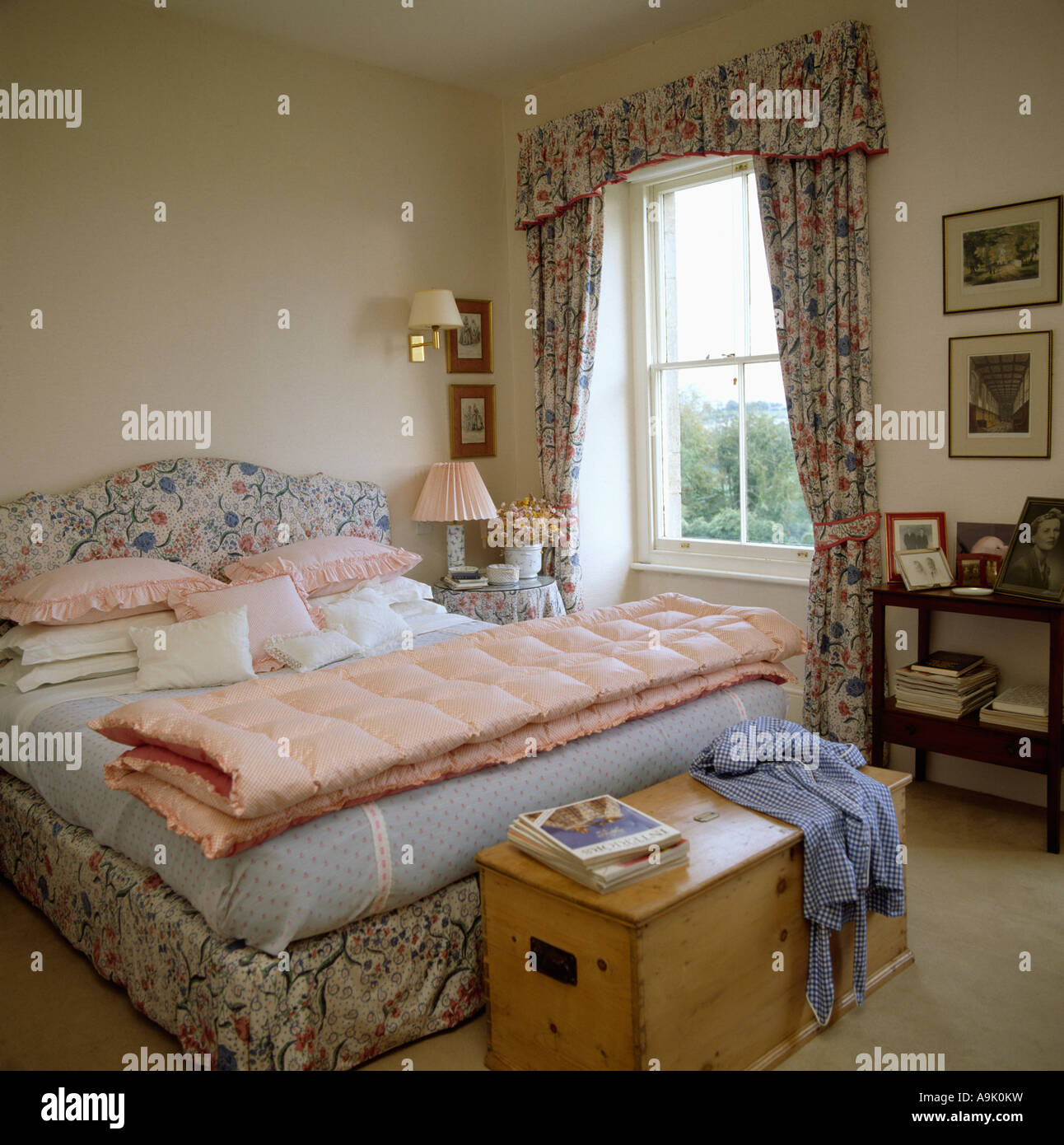 Pink quilt on bed with upholstered floral headboard and matching curtains in bedroom with pine chest below the bed