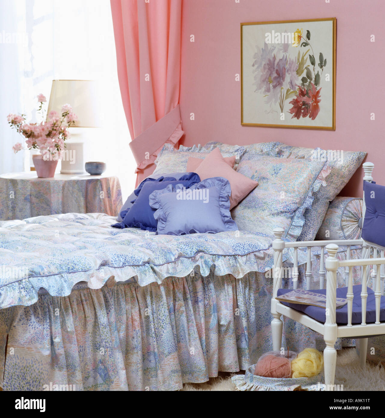 Blue cushions and patterned blue quilt on bed in pastel pink bedroom ...