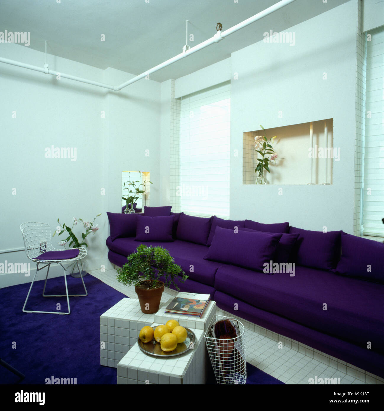 Purple Sofa Along The Length Of A Wall In White Eighties