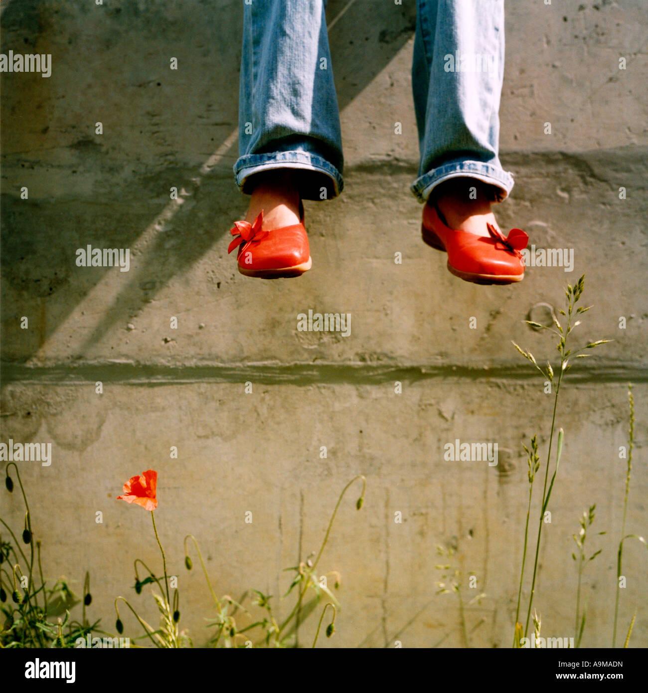 dangle feet over poppy flowers - Stock Image