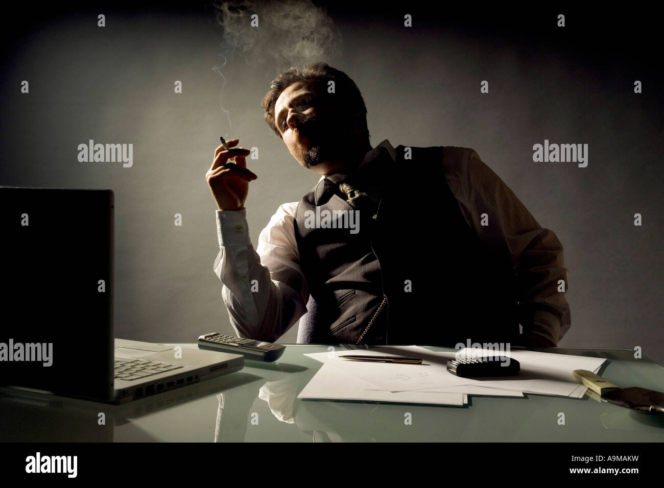 businessman smoking in his office - Stock Image