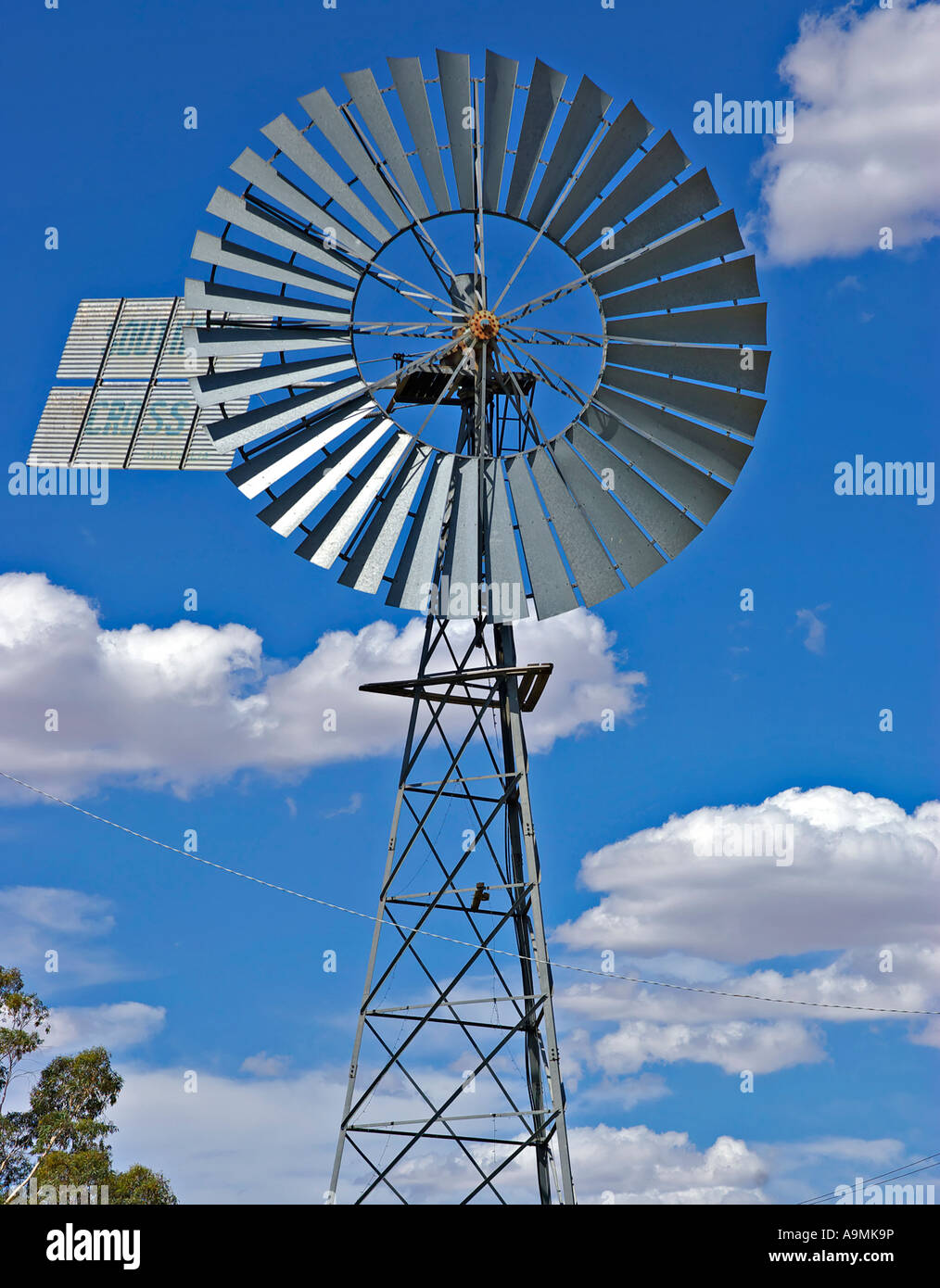 a big silver metal windmill in front of a nice cloudy blue sky - Stock Image
