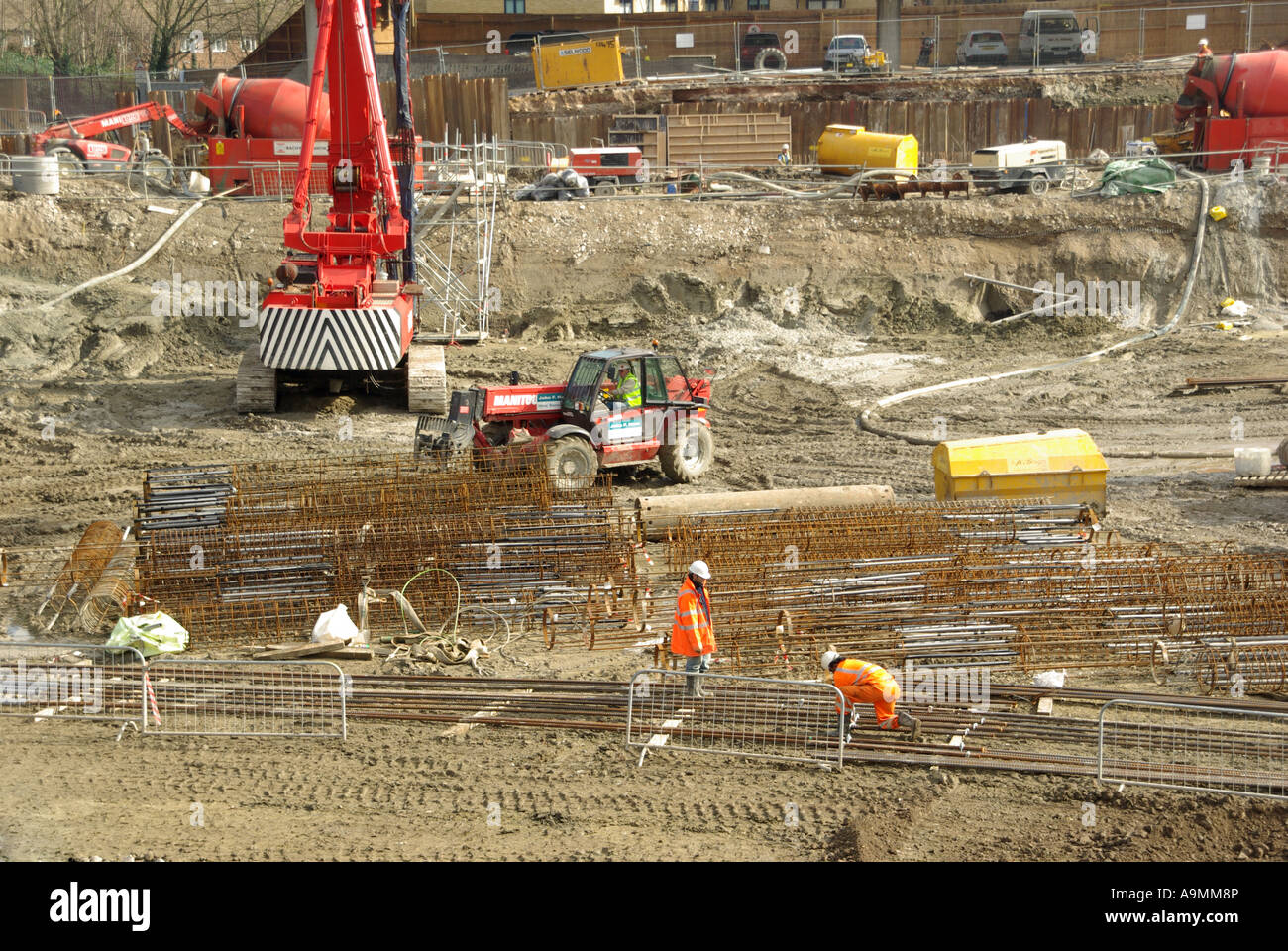 Construction site workmen assemble steel reinforcing cages ready for dropping into pile bores for concreting Stock Photo