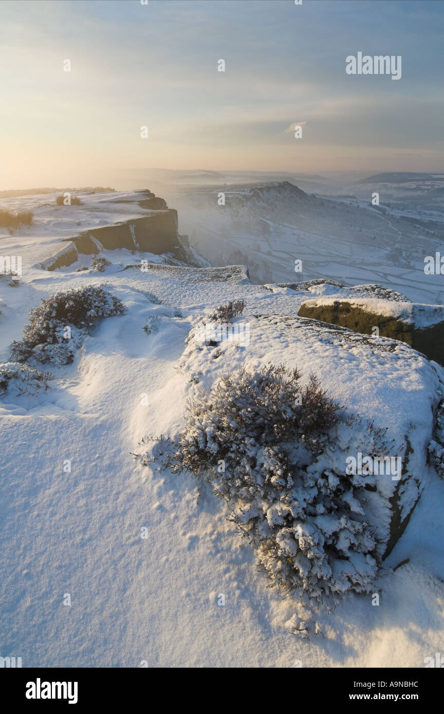 Sunrise on a misty winter morning with snow on Froggatt edge derbyshire peak district national park England UK GB Stock Photo