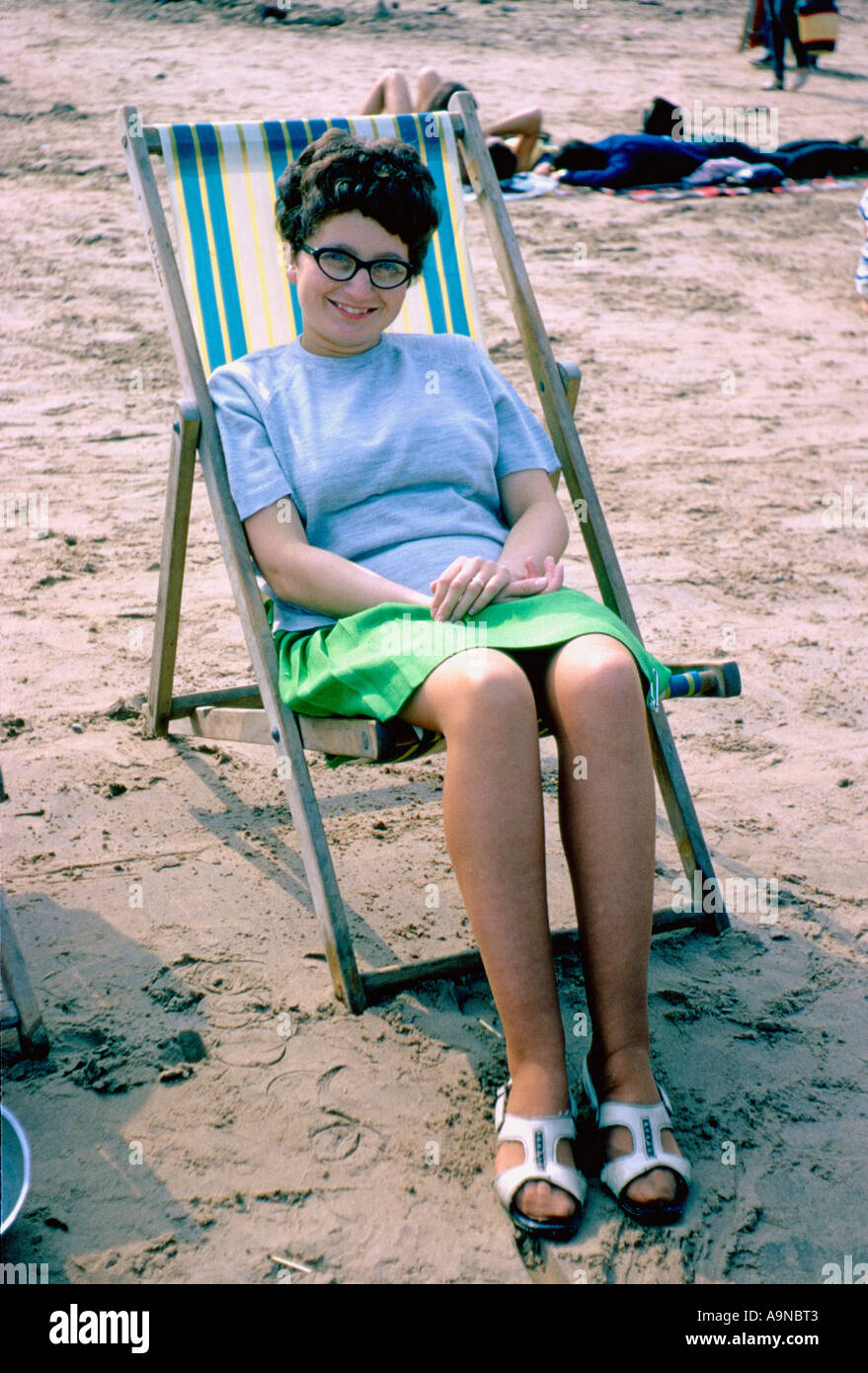young woman in deckchair at beach in 1960 s - Stock Image