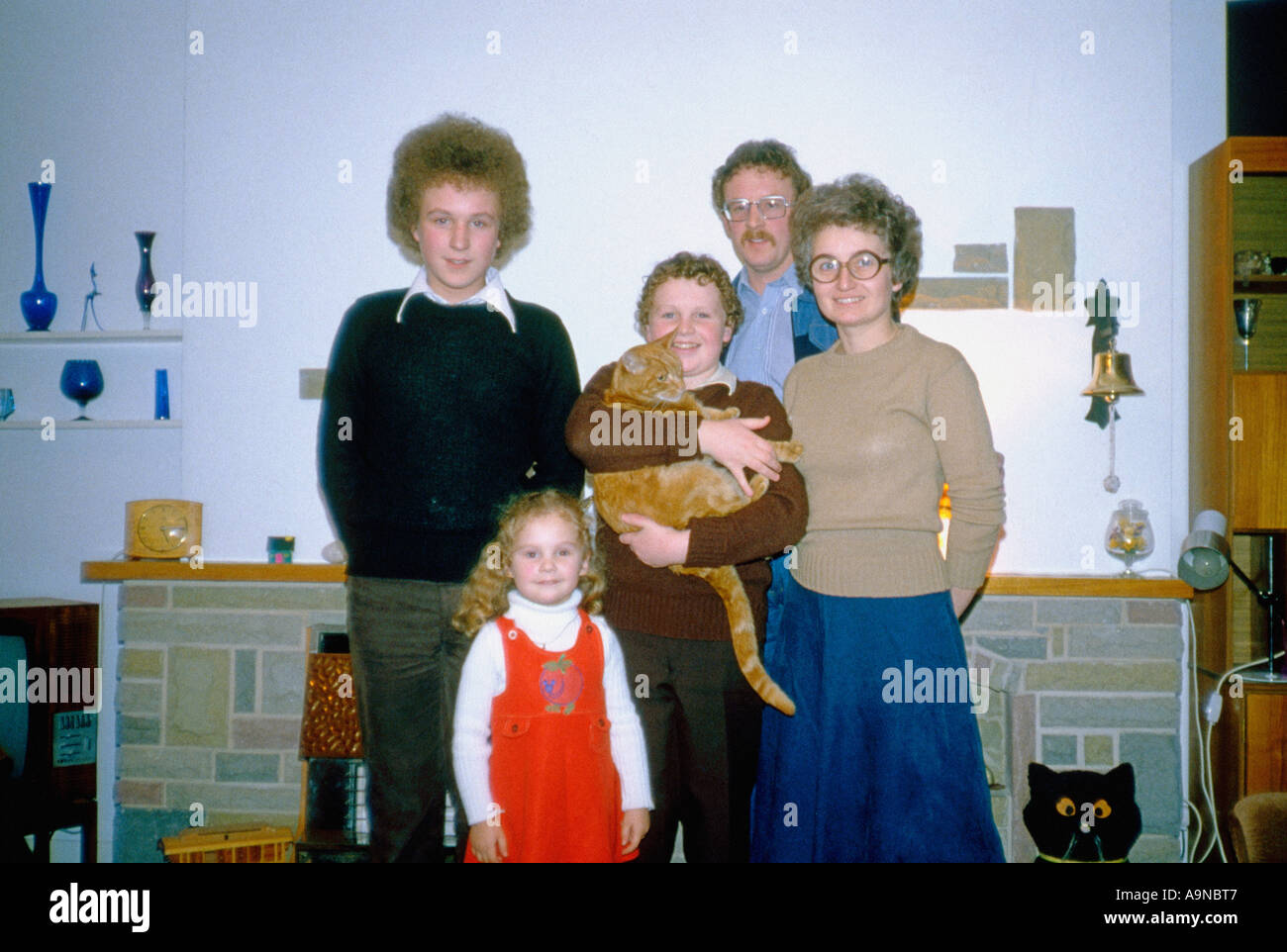 1970 s shot of family in their lounge with pet cat - Stock Image