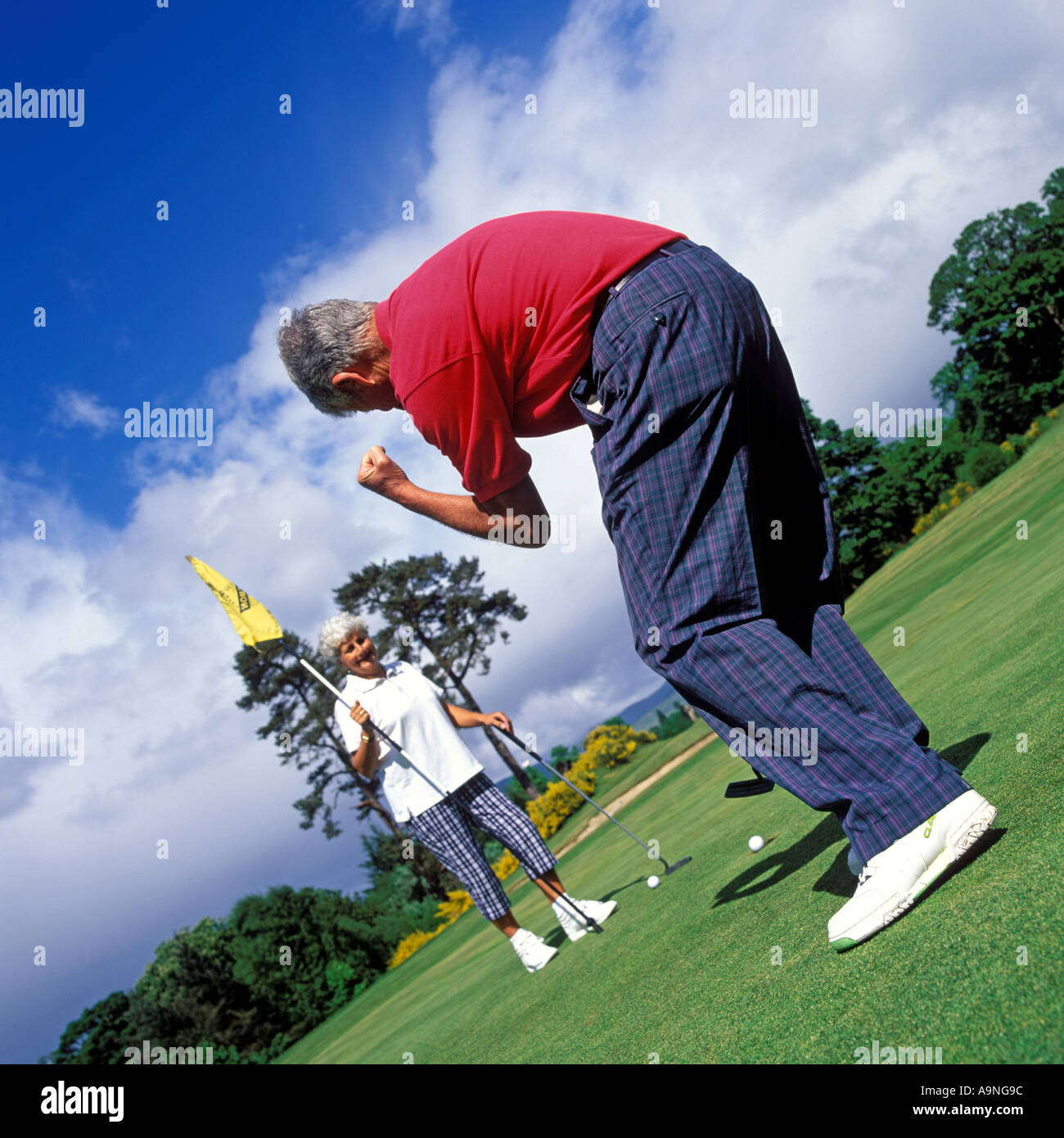 COUPLE GOLFING IN SCOTLAND ON A COURSE IN MAY - Stock Image
