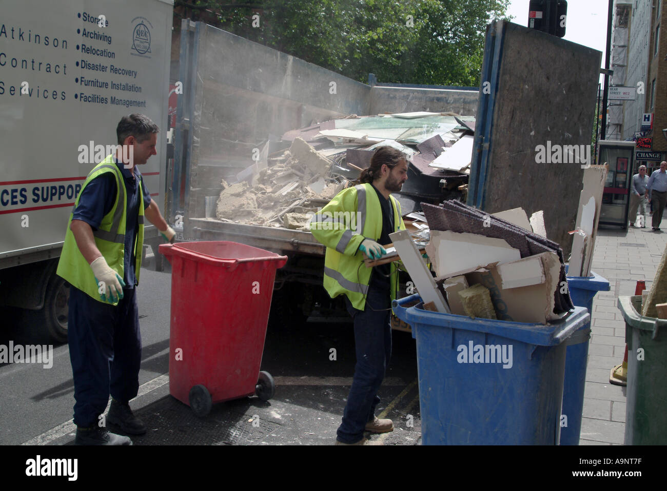 TWO COUNCIL WORKERS COLLECTING THE RUBBLE IN THE CITY LONDON 2005 - Stock Image