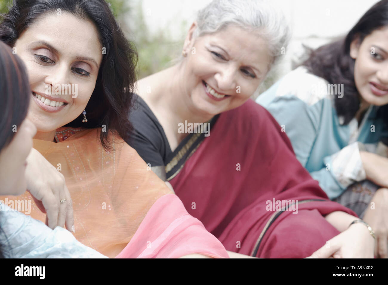 Four women sitting together smiling - Stock Image