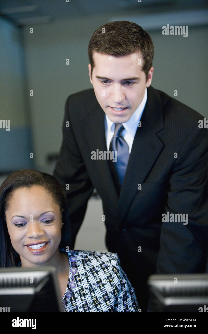 Two business people looking at a computer monitor - Stock Image