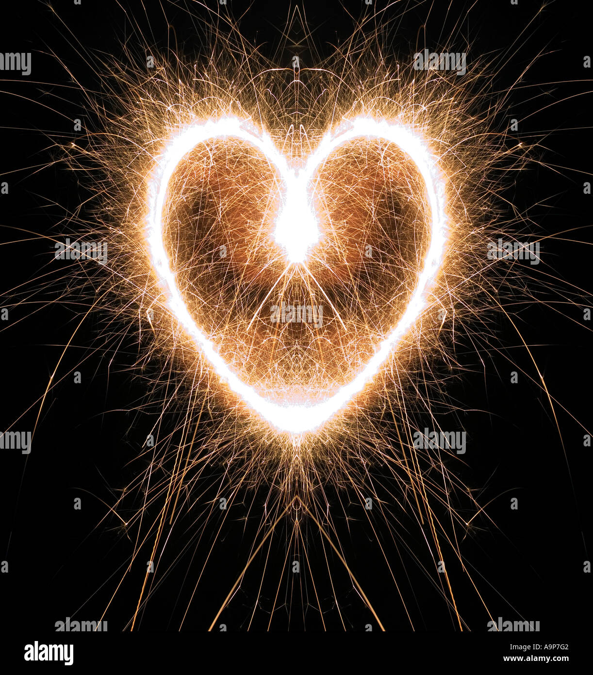 Sparkling heart shape made at night with sparklers - Stock Image
