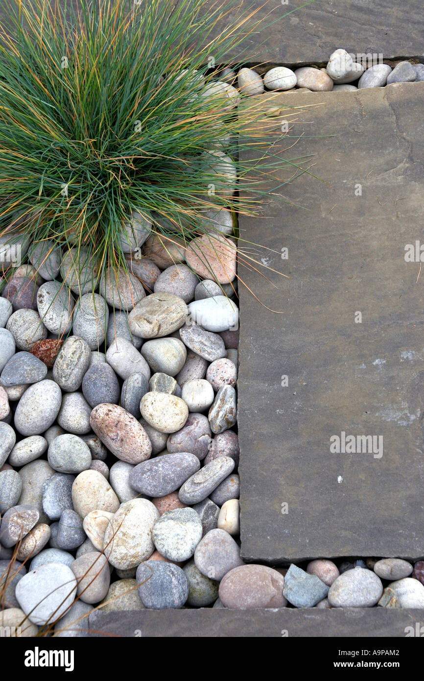 garden design stone slab against pebbles and blue grass stock image