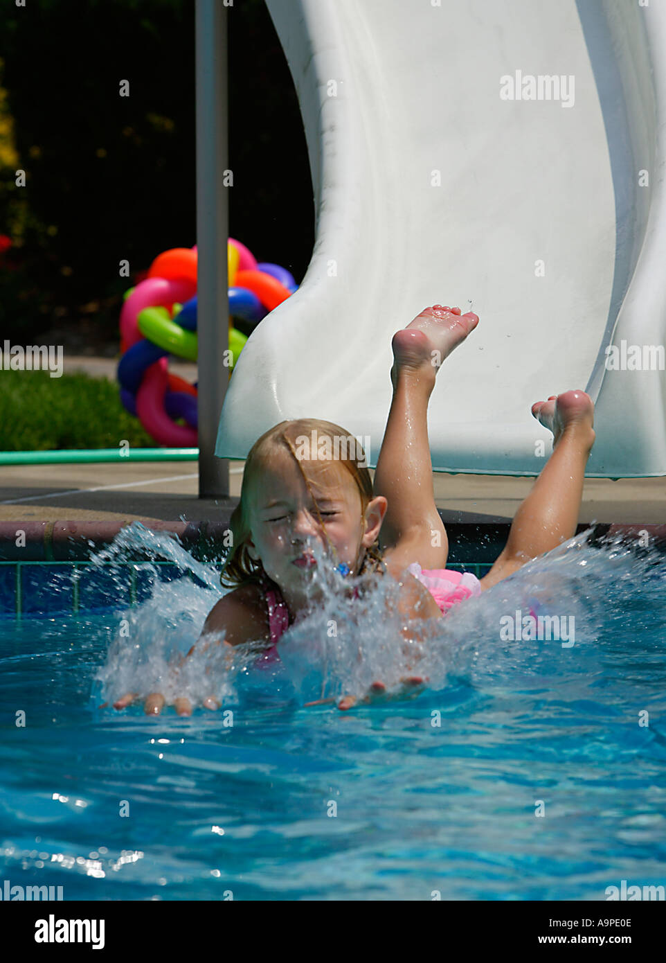 Child Sliding Into A Swimming Pool   Stock Image