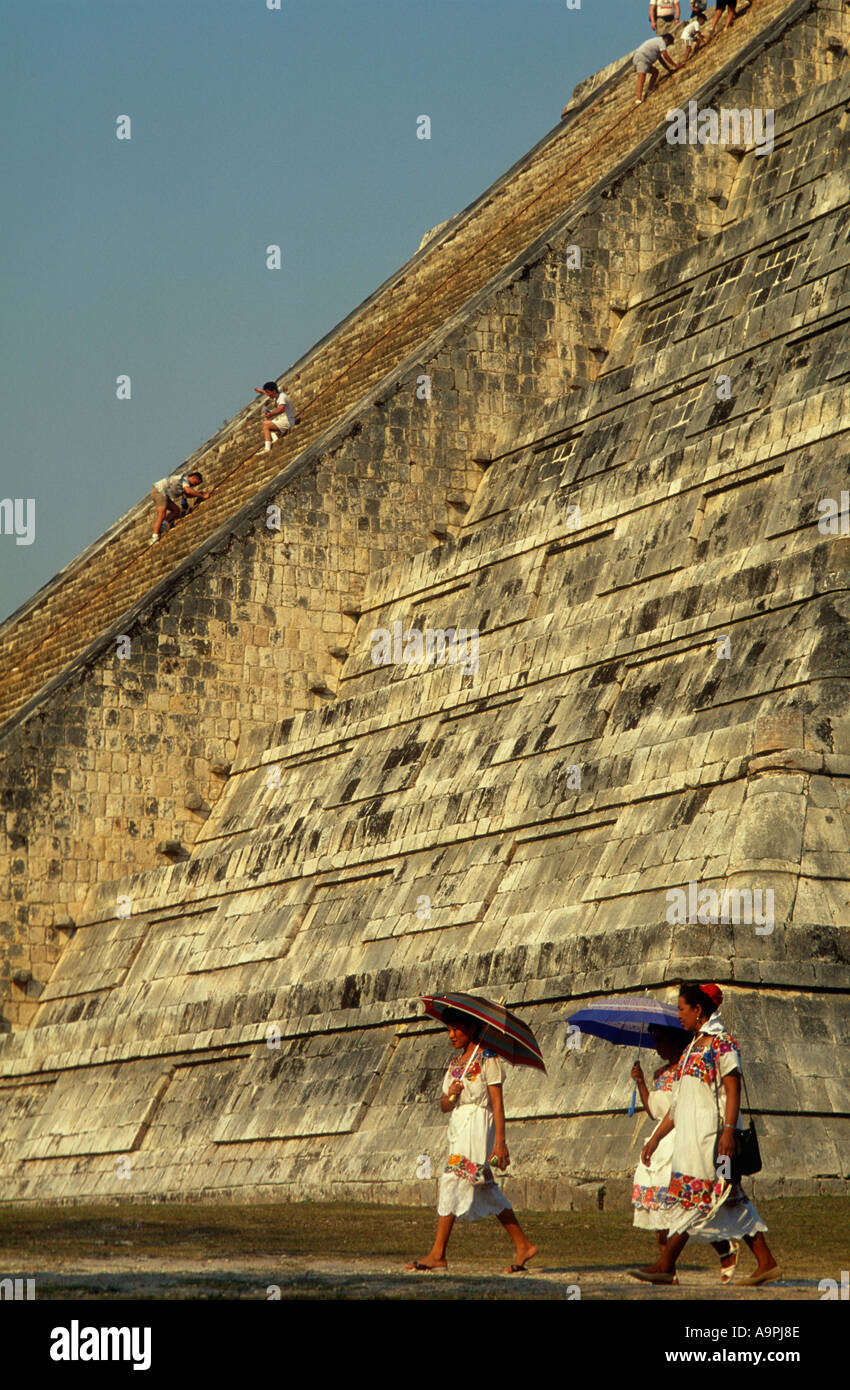 Mexico Yucatan State Chichen Itza El Castillo Mayan women walking past pyramid - Stock Image
