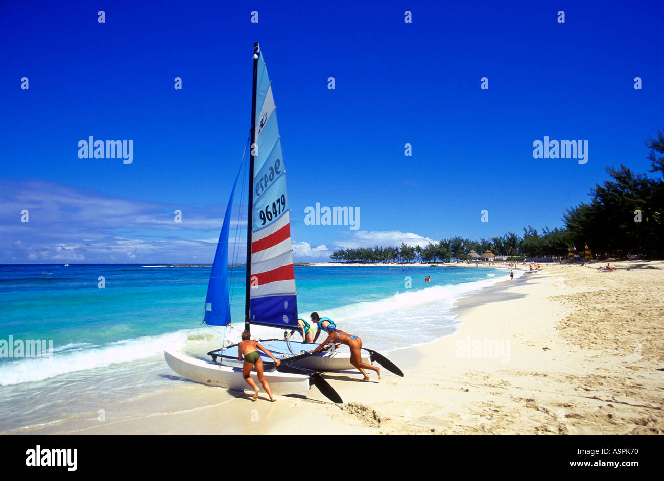 Bahamas Nassau beach scene group of four people pushing a catamaran into the sea - Stock Image
