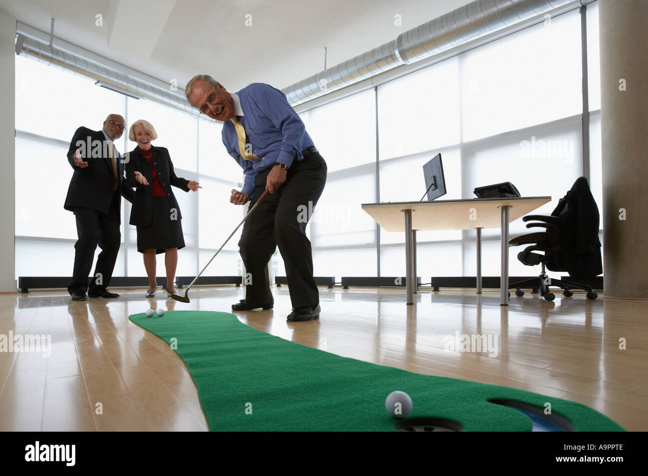 Three senior office workers practicing putting - Stock Image