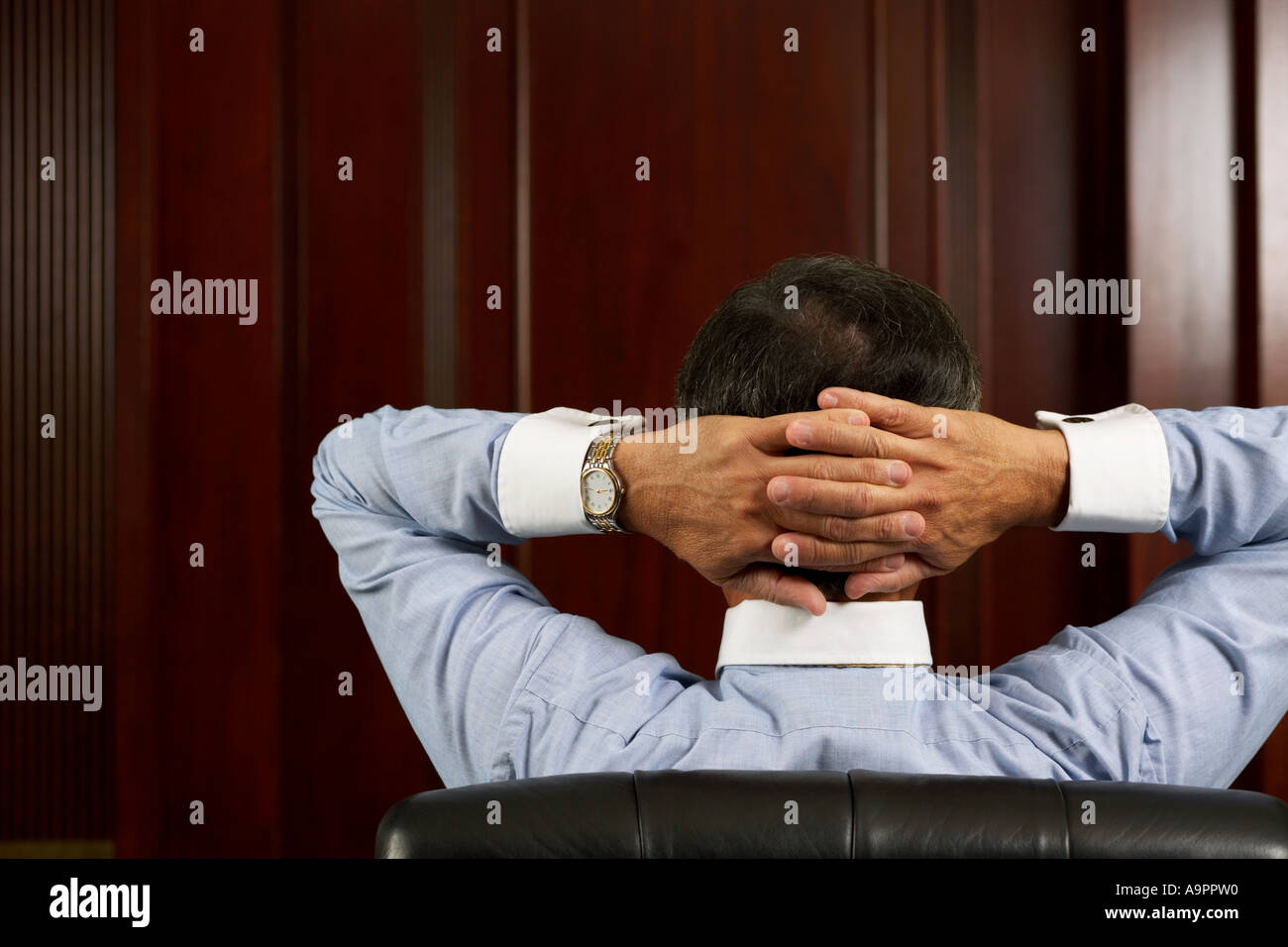 Businessman relaxing with hands behind head - Stock Image